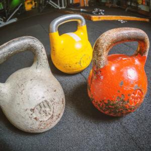 Three kettlebells on a floor in gym